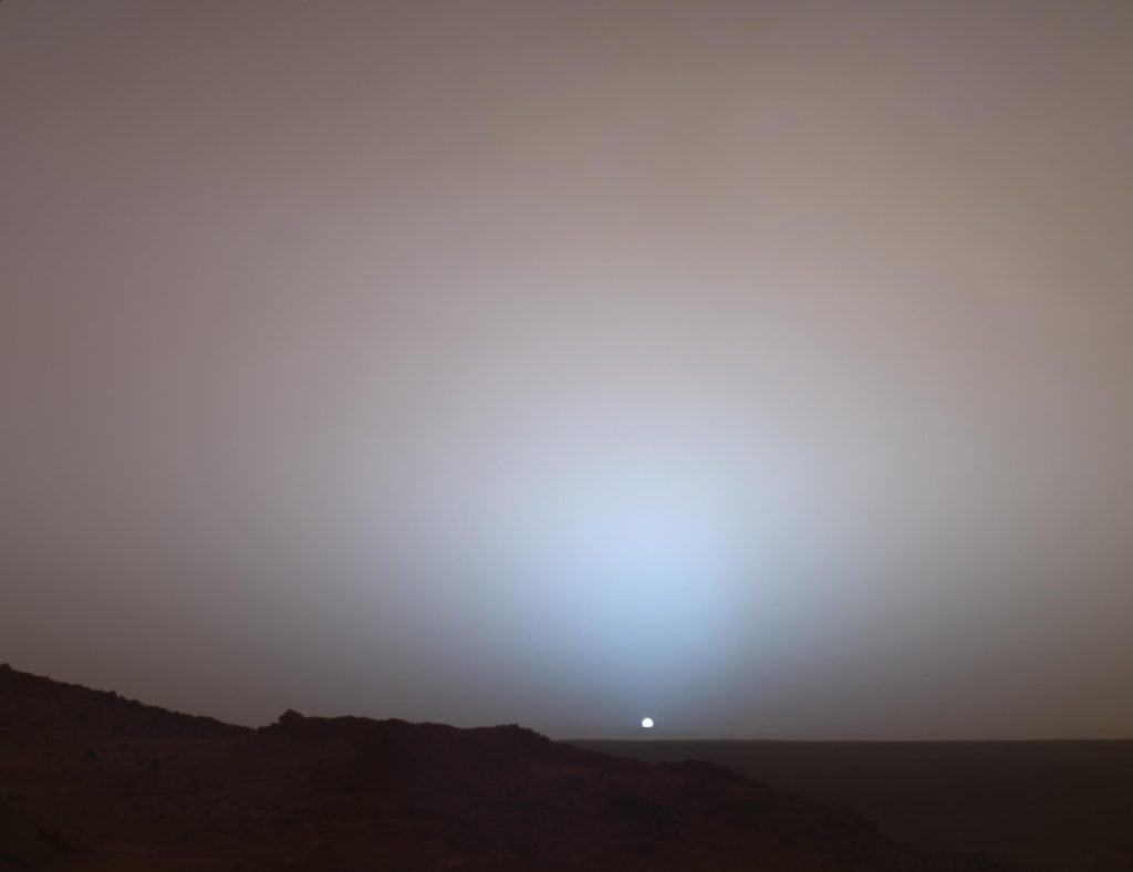 A small sun sets on a planet devoid of complex life. Image Credit: NASA/JPL/Texas A&M/Cornell